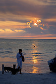Woman walking dogs on the beach enjoying the sunset over Holbox island, Quintana Roo, Yucat�n Peninsula, Mexico,