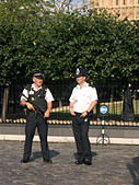 Armed Police officers guard the Houses of Parliament, London, England