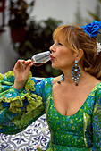 Blond Spanish woman drinking glass of fino sherry, Fuengirola Feria, Andalucia, Costa del Sol, Spain, Europe
